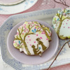 Closer View of Pink Cookie with Man-Proposing Foreground Element: Cookies and Photo by Julia M Usher; Stencils Designed by Julia M Usher with Confection Couture Stencils